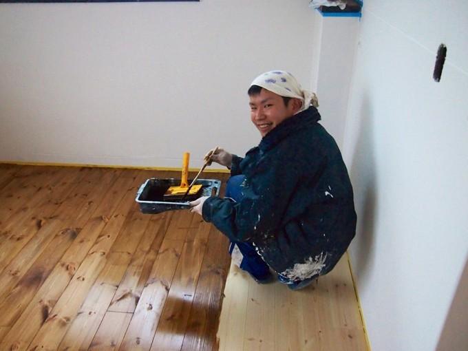 新しく貼り替えた床をオイルで仕上げる悠作さん。