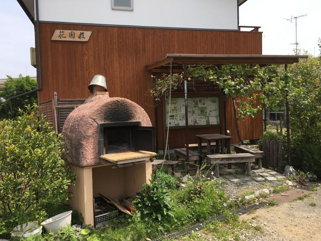 広場に面したブドウ棚とピザ釜